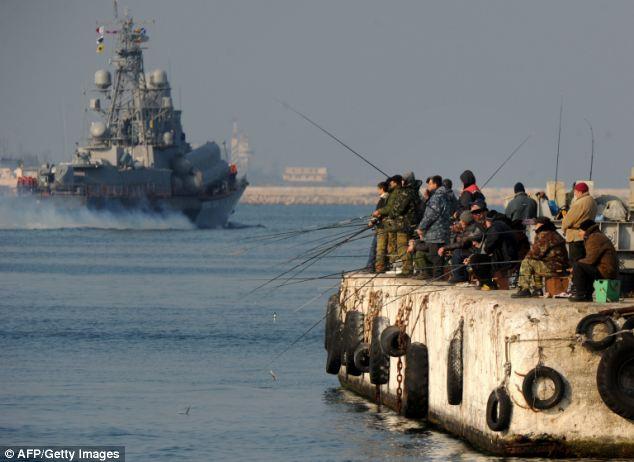 Crimean fishermen on a pier as a Russian naval vessel passes them in Sevastopol Bay