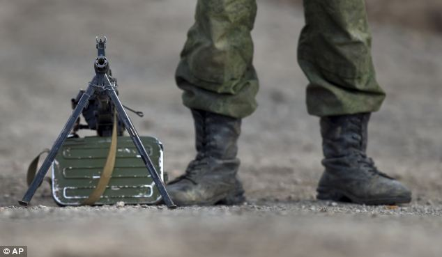 A Russian soldier stands next to a machine-gun outside the Ukrainian infantry base in Perevalne