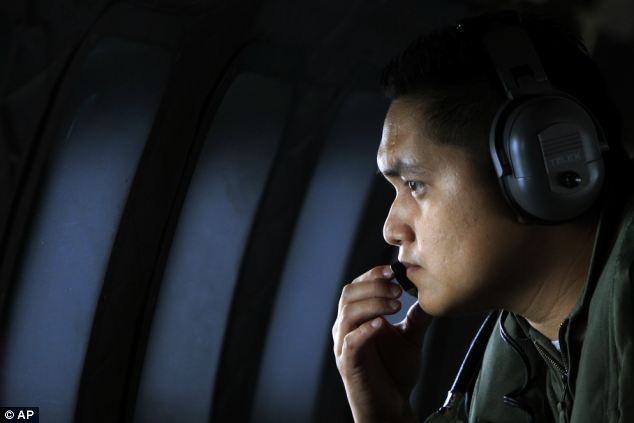 A crew member of a Royal Malaysian Air Force CN-235 aircraft looks out of the window during the search and rescue operation for the missing Malaysia Airlines plane