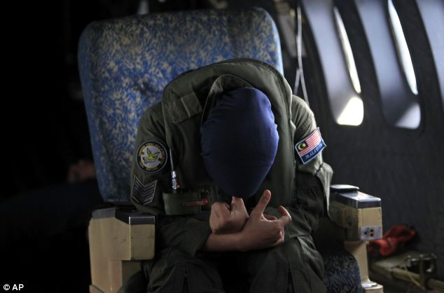 A crew member of a Royal Malaysian Air Force CN-235 aircraft rests after long hours working in a search and rescue operation for the missing plane