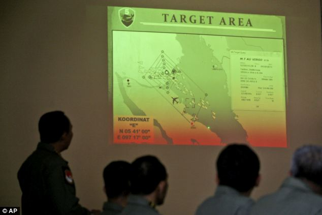 Indonesian Air Force officers examine the projection of a map that shows their operation area over the Strait of Malacca during a briefing following a search mission