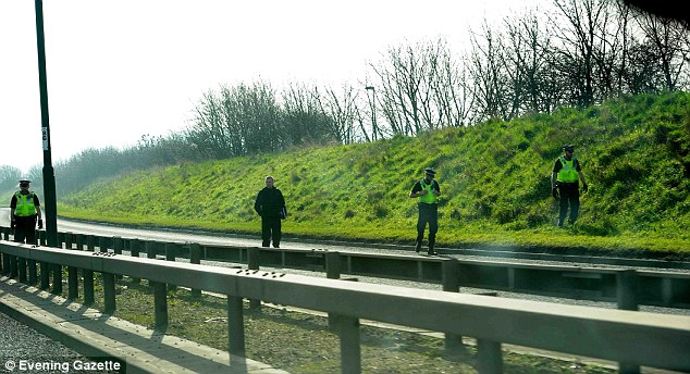 Officers search the verge of the dual carriageway for the man's organ and other forensic evidence