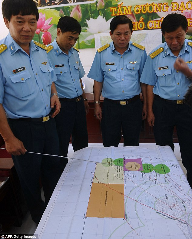 Search effort: Colonel Do Duc Minh (far left) Vietnam Air Force's 370 Division's Chief of Staff, points at a map as he speaks to reporters about search flights aimed at finding the missing Malaysia Airlines plane
