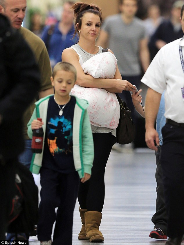 A rare day off: The 32-year-old hugged a pillow as she strolled through an airport with son Sean Preston