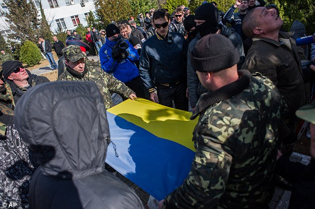 Ejected: Ukrainian soldiers fold a Ukrainian flag removed by the Crimean pro-Russian self-defence force after they were forced to leave Ukrainian Navy headquarters