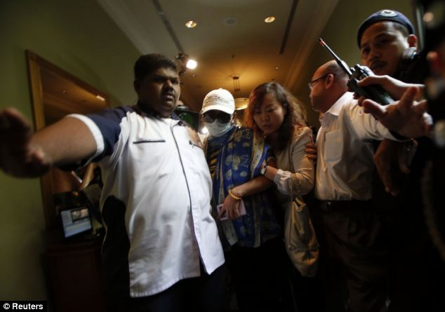 Chinese family members of missing Malaysia Airlines MH370 passenger are escorted away from the media outside the media conference area at a hotel near Kuala Lumpur International Airport