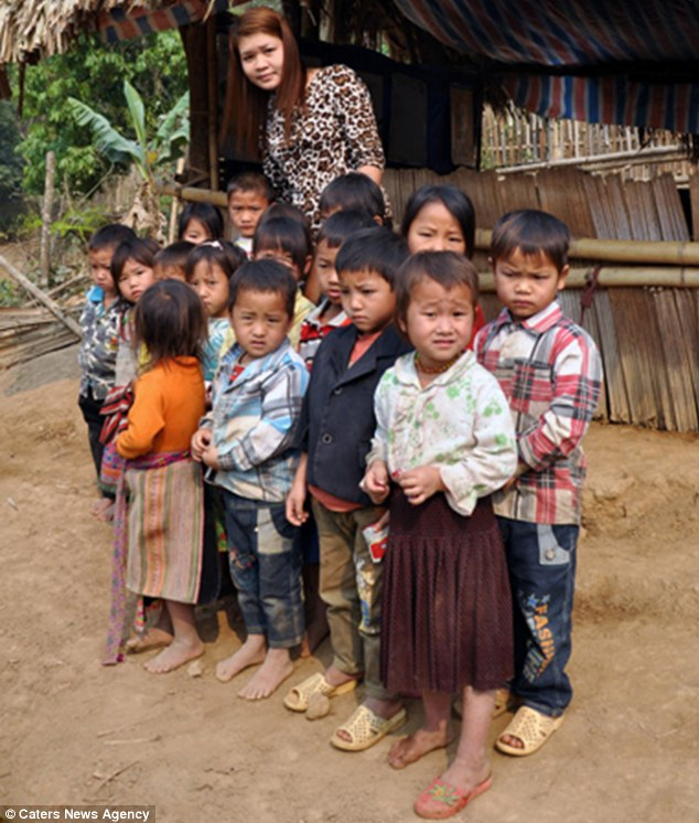 Safe on the other side: Teacher Tong Thi Minh pictured with the class who were taken across the river in bags