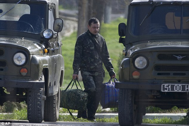 Packing up: A Ukrainian air force officer carries his bags out of the Belbek airbase, outside Sevastopol, Crimea, on Thursday as Kiev announced plans to withdraw 25,000 troops from the peninsula