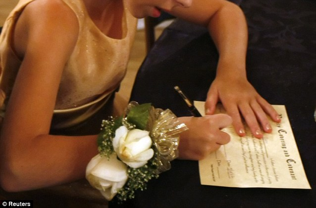 A young girl signs the purity covenant as a witness: It states that her father, as High Priest of the household, will now protect her virginity
