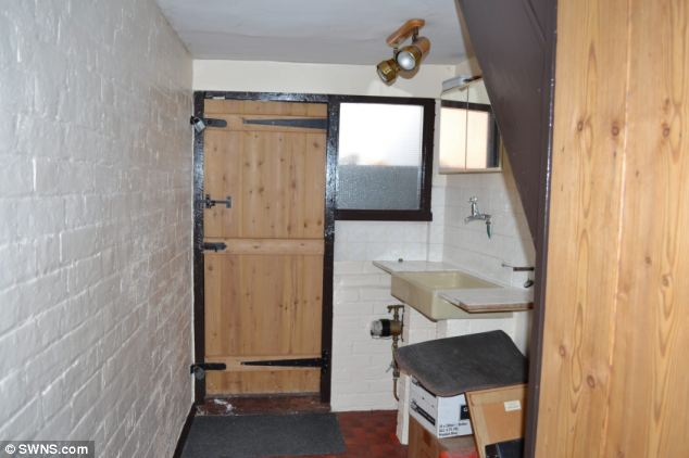 This tiny two-bedroom home in Colchester, Essex, has gone on sale for £77,000 despite not having an indoor toilet. Pictured is the home's modest kitchenette, which appears to lead towards the garden and shed