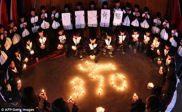 Mourning: High school students hold candles during a vigil for passengers of the missing Malaysia Airline flight MH370 in Lianyungang, China