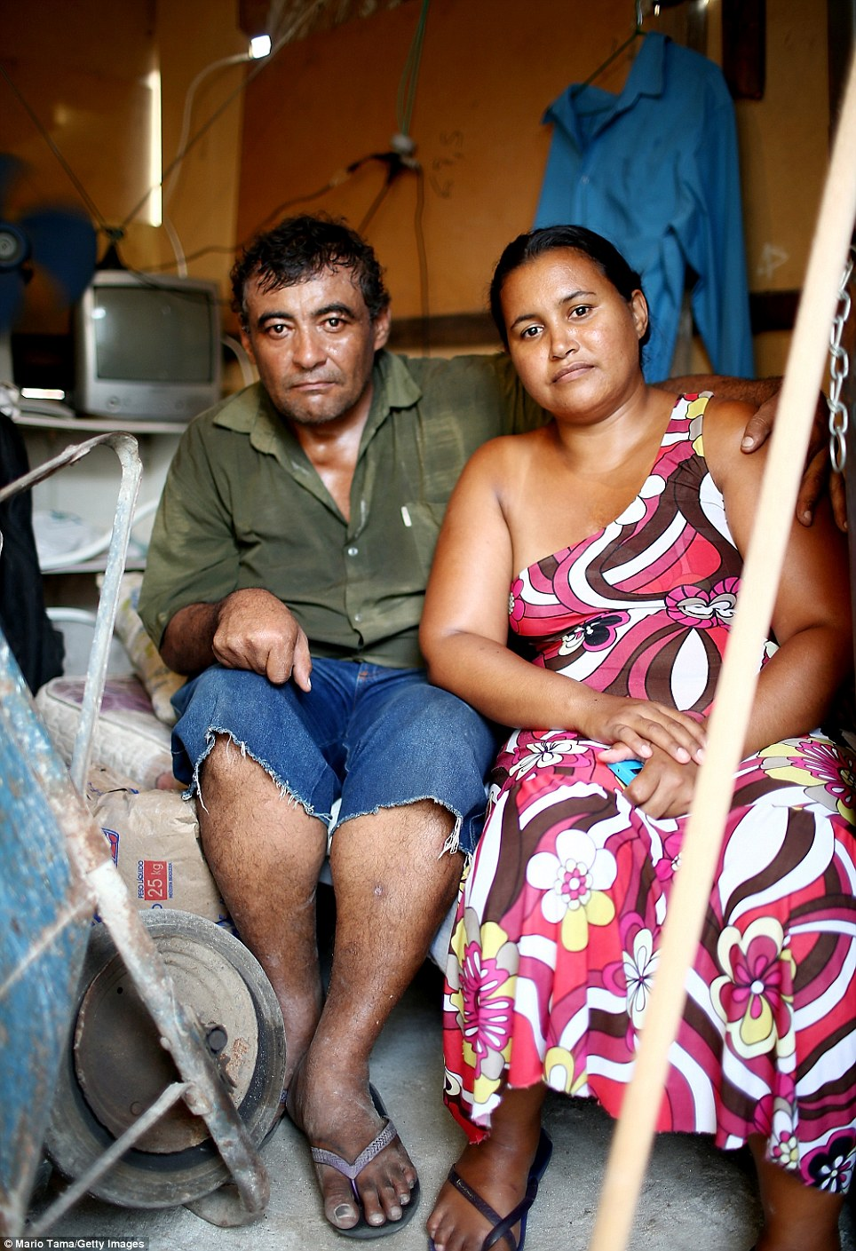 Joao Batista da Silva (left) and wife Gizelda Alves da Silva pose on their bed in the Complexo da Mare slum. Police have been criticised for violent control tactics in the slums. Last year, police were charged after bricklayer Amarildo de Souza, who lived in the city's biggest shanty town Roncinha, was tortured and murdered