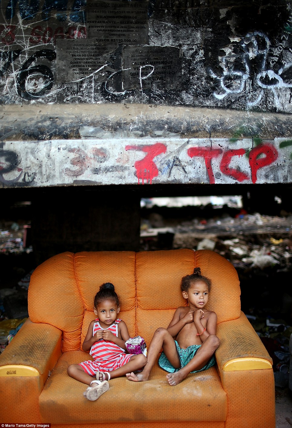 Pacification officers, known as the UPP, will soon occupy and control life within the slum. UPP officers come in after federal troops 'clean-up' a slum imprisoning drug dealers in an attempt to rid the favela of crime. Pictured behind the children are community posters advertising items that are up for sale