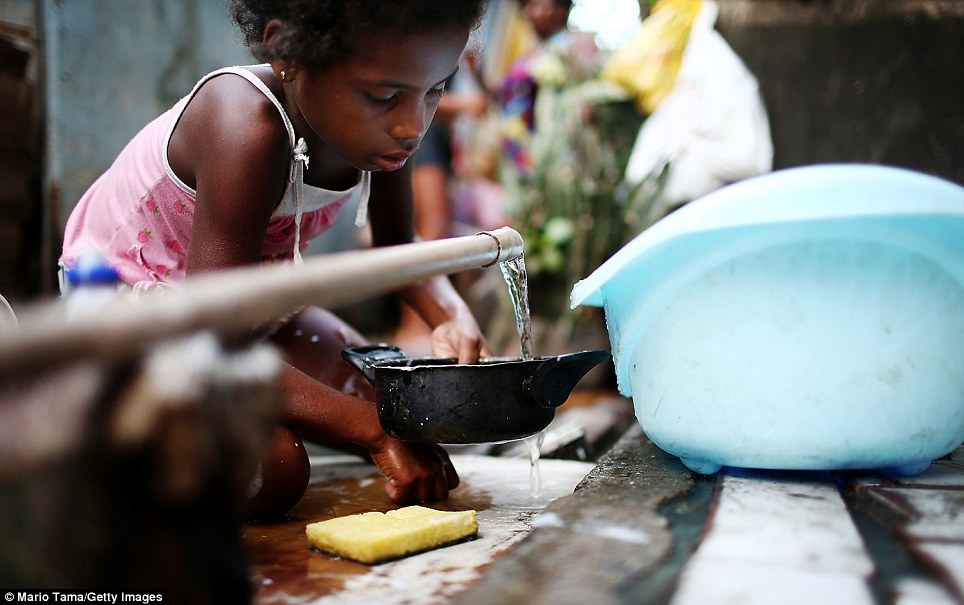 Jessica washes dishes at the one with with running water available to dozens of residents in the area. The Brazilian government has claimed that the clean-up operation will improved the quality of life of favela residents'