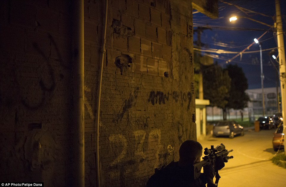 One soldier hides behind a wall as he point his gun towards the street. It was dusk in Rio when troops entered the favela