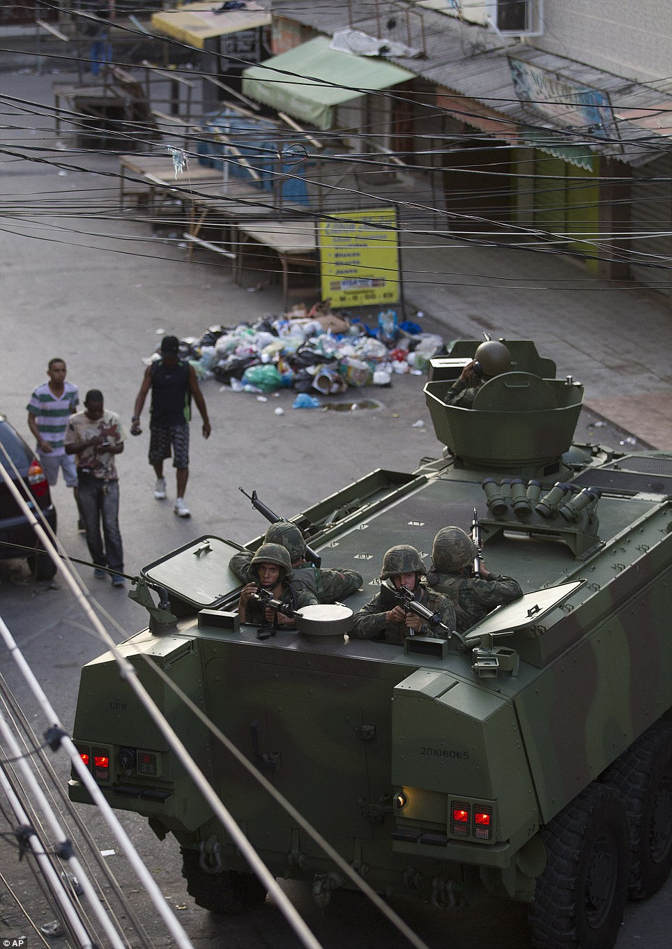 Residents walk through the slum as dozens of police officers, in camouflaged uniform hold machine guns from behind heavy-duty navy trucks