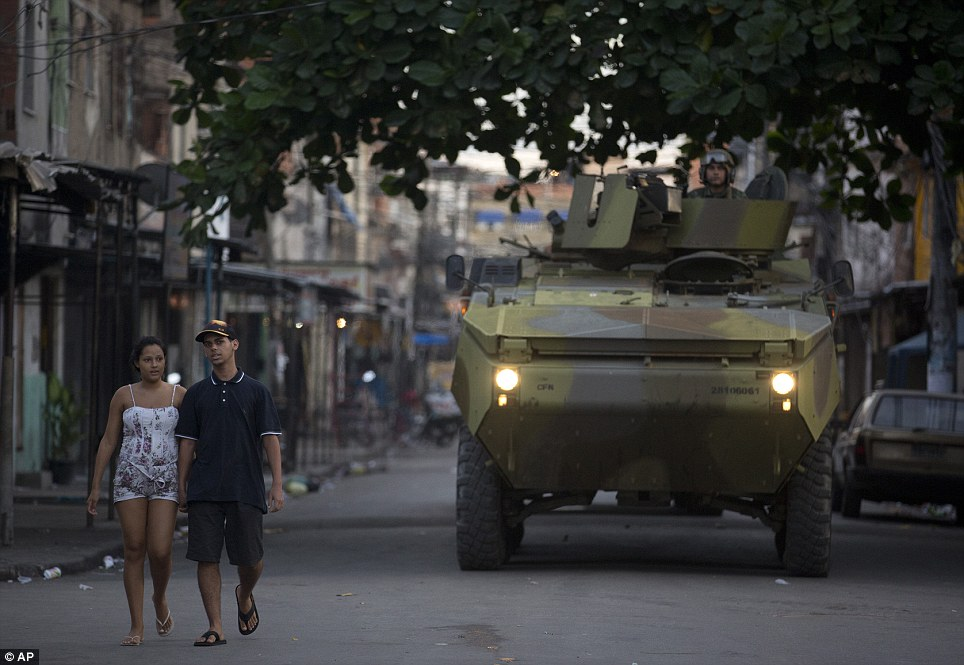 A couple walks along as a navy tank storms into the place where they live. The army presence in favelas across Rio has sparked rage across the city. Last week, protestors set fire to a police office in the city