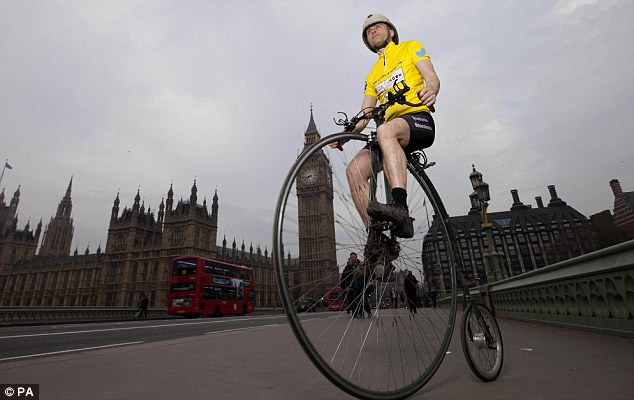 Look, no hands! Joff on his home-made penny farthing cycling along Westminster Bridge in London