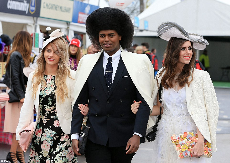 Looking good: Fashion blogger Prince Cassius (centre) and two glamorous friends make their way into the Aintree racecourse for a day out at the races