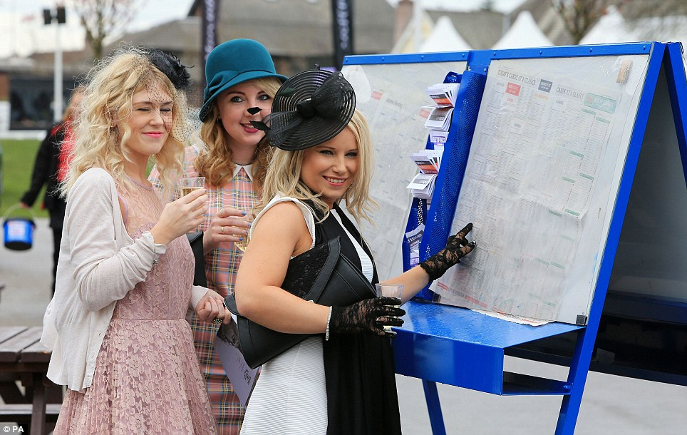 Place your bets! A trio of racegoers show off their elegant frocks and fascinators while checking the form as they prepare to place their bets on Ladies Day