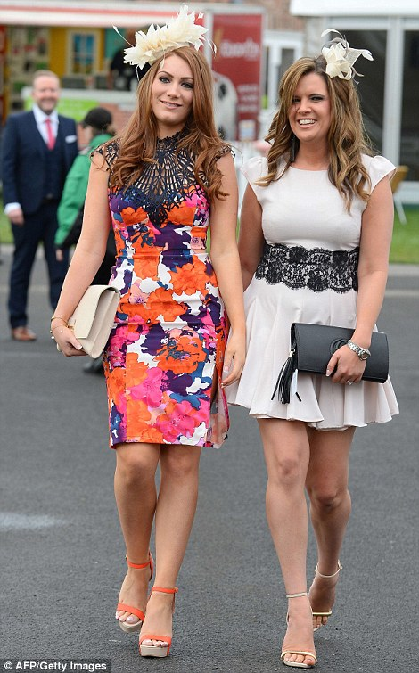 A pair of elegant racegoers arrive