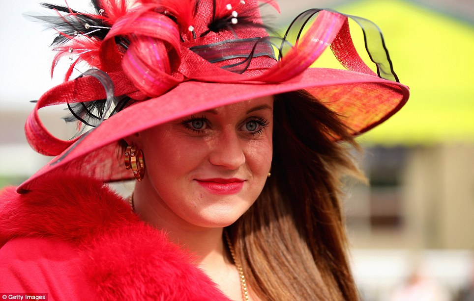Lady in red: A racing aficionado shows off her impressively large crimson headpiece, which was clearly chosen to match her scarlet coat and lipstick