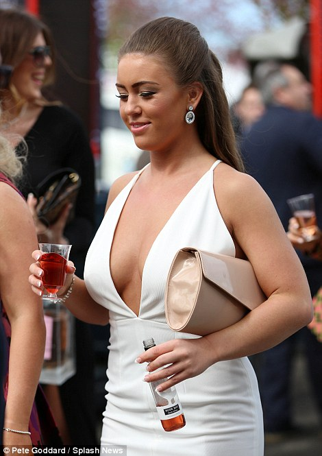 A racegoer flashes the flesh while drinking a glass of wine