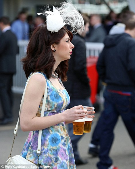 A racing fan shows off her poppy print dress