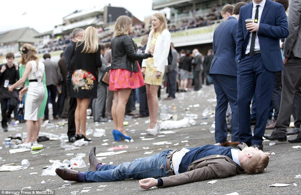 The day's fun became too much for one drunken reveller who is pictured lying on the ground as the races drew to a close
