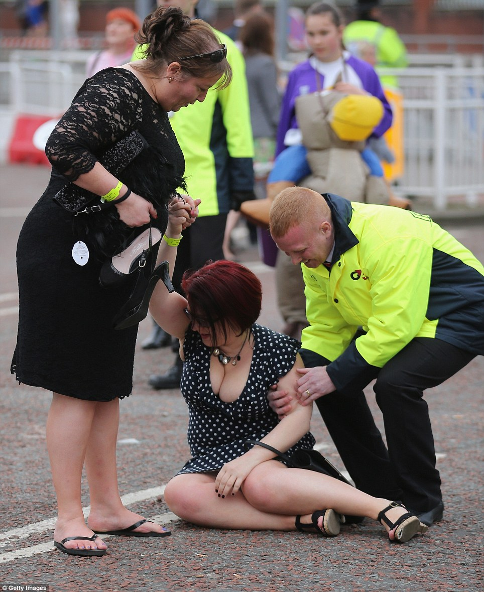 Struggling to walk: One woman had to be helped up by security staff after she toppled to the ground
