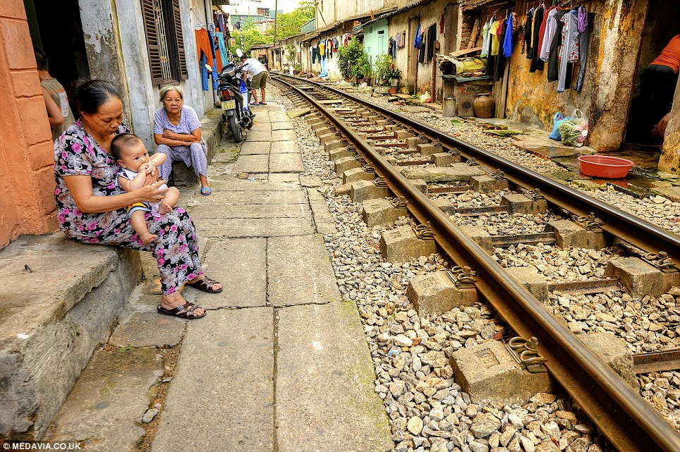 Dangerous: A woman with a baby on her knee by the track. The line is so close to shops and homes that huge trains are forced to squeeze past market traders