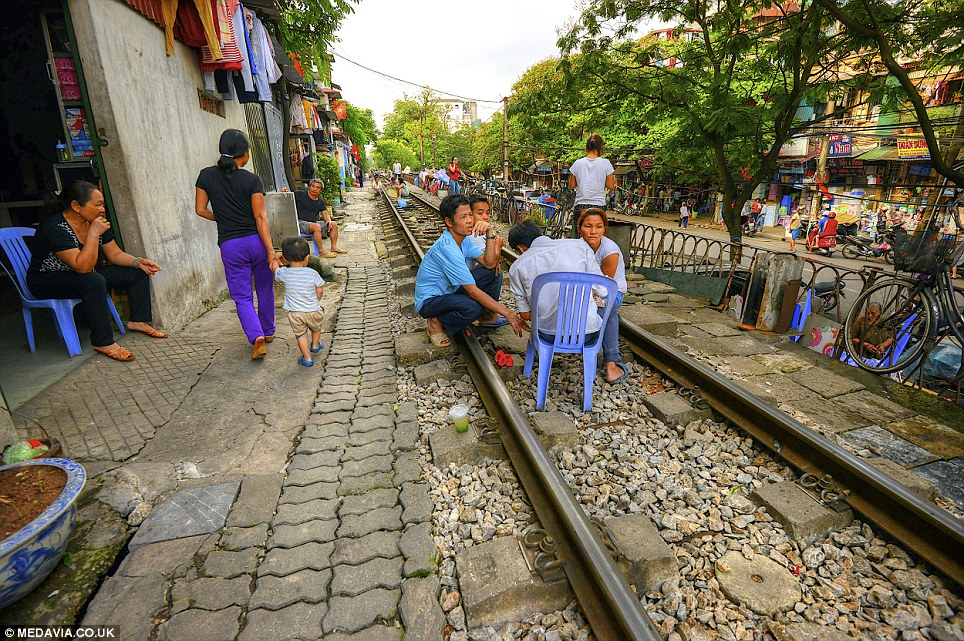 On the line: The track is so close to buildings that locomotives, which negotiate the line twice a day, brush past pedestrians and children playing in the street