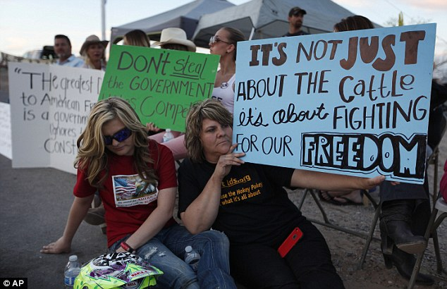 A higher cause: Krissy Thornton, right, and Burgundy Hall protest Wednesday with others - they say the cows are a proxy for the freedoms of all Americans