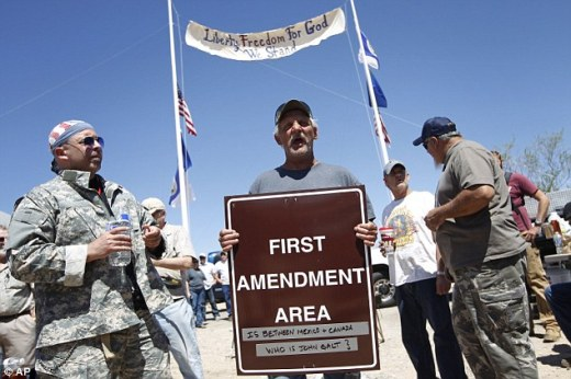 They won't go: Charlie Brown holds up a sign Thursday from the Bureau of Land Management's 'first amendment area' during a protest of the Bureau of Land Management's roundup of cattle near Bunkerville