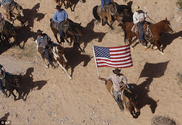Victory: The Bundy family and their supporters fly the American flag as their cattle were released by the Bureau of Land Management back onto public land outside of Bunkerville, Nevada