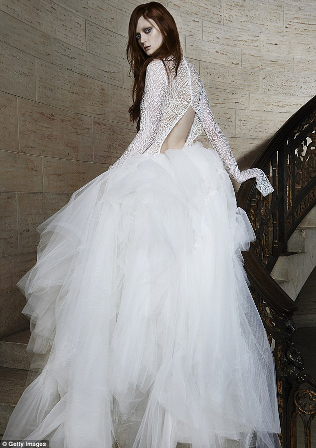 Not your average wedding dress: A model poses on a marble staircase wearing a long-sleeved gown with an intricate lace detail and edgy open back