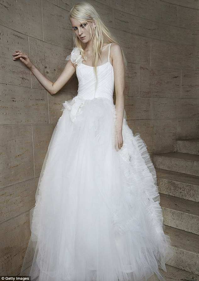 Here comes the bride: A more traditional look is this simple ensemble with a lace embellishment on one shoulder