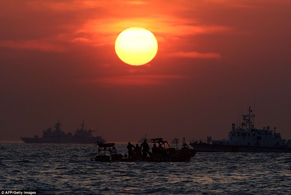 Rescue workers are pictured against the backdrop of a sunset in Jindo. Relatives have blasted a top coastguard official saying that not enough is being done to retrieve bodies still trapped in the vessel