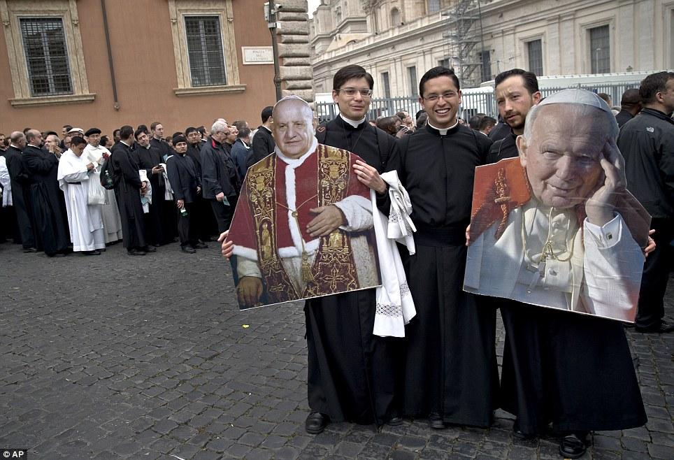 Celebrado: Sacerdotes segurar fotos do Papa João XXIII (à esquerda) e João Paulo II (à direita) na Praça de São Pedro, no Vaticano