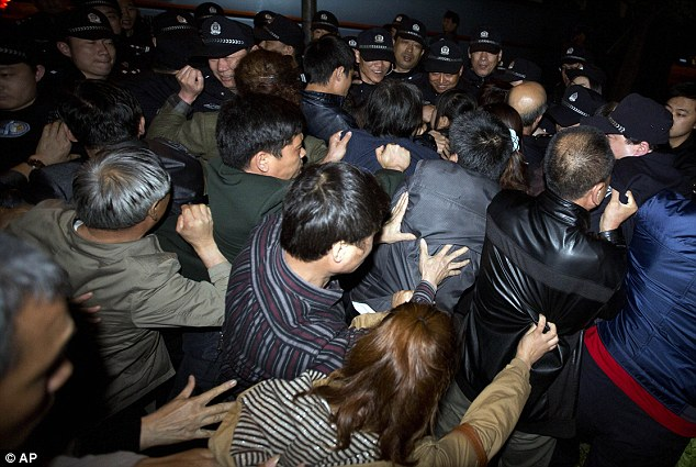 Relatives of Chinese passengers onboard the Malaysia Airlines MH370 push through a police line to march to the Malaysian embassy in Beijing on Thursday