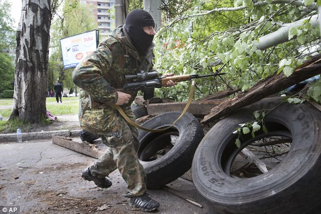 Ready for battle: A Pro-Russian gunman runs behind barricades in Slaviansk. The action came a day after Putin said that Ukraine should withdraw its military from the eastern and southern regions of the country