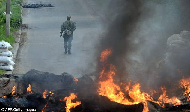 An armed pro-Russian man walks past burning debris at a checkpoint in the southern Ukrainian city of Slavyansk