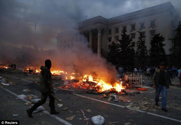A protestor walks past a pro-Russian tent camp which was set alight during clashes with Ukrainian nationalists