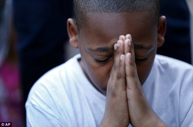 Praying: A young boy folds his hands in prayer during a prayer vigil for Martin Cobb at Abundant Life Church on Richmond's south side on Saturday