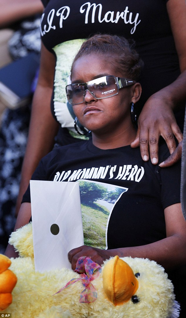 Suffering: Sharain Spruill, whose daughter was allegedly raped and son was killed on Thursday, grieves at her son's prayer vigil on Saturday
