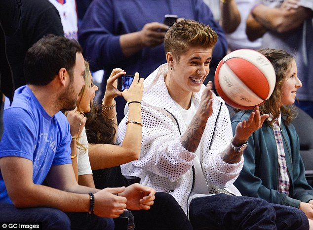 Playing like a kid! Pattie snapped a photo of her famous boy gleefully playing with a basketball as they sat courtside