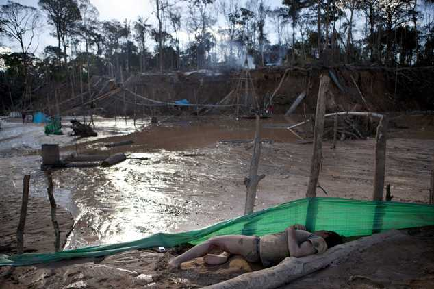 In this May 4, 2014 photo, a miner naps near his workstation in La Pampa in Peru's Madre de Dios region. Thousands of artisanal gold miners sweat through the...