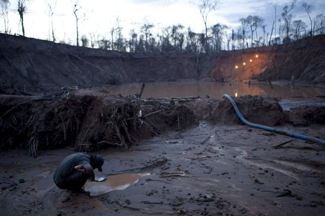In this May 3, 2014 photo, an informal miner works to separate flecks of gold from the sandy, alluvial soil, using mercury to bind inside the crater of a gol...