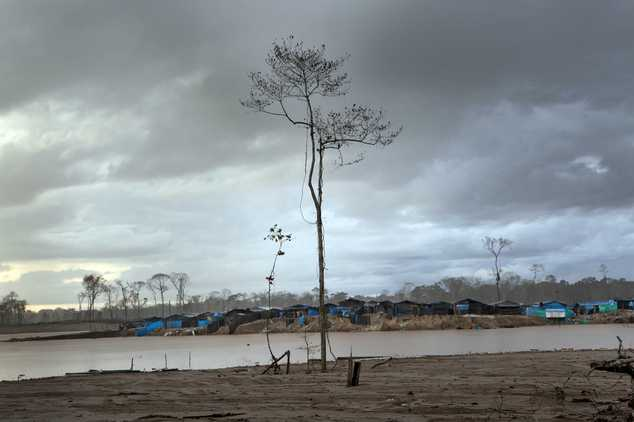 In this May 4, 2014 photo, a mining camp lines the horizon in La Pampa in Peru's Madre de Dios region. Since artisanal gold mining took hold in La Pampa, min...