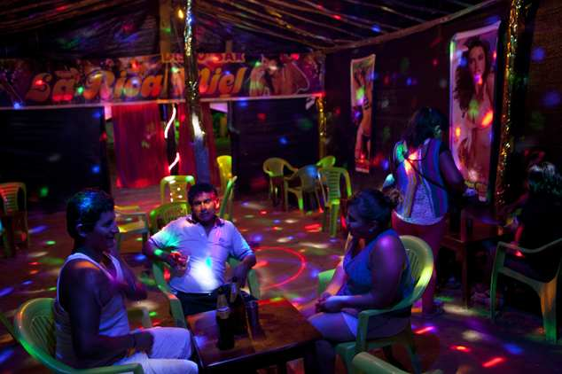 """In this May 3, 2014 photo, a sex worker sits with potential customers at the informal bar """"La Rica Miel"""" or Delicious Honey in English, in La Pampa in Peru's..."""
